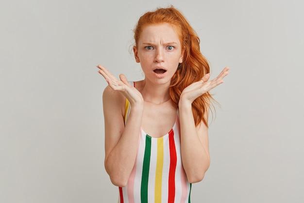 Marszcząca brwię pani, niezadowolona kobieta z rudym kucykiem i piegami, ubrana w kolorowy kostium kąpielowy w paski