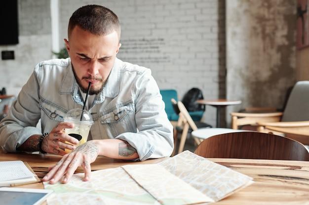 Marszczący brwi brodaty mężczyzna w dżinsowej kurtce siedzi w kawiarni i pije zimną kawę, szukając najlepszych miejsc do odwiedzenia za pomocą mapy