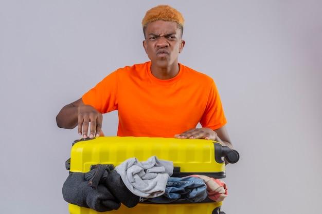 Marszczący brwi chłopiec ubrany w pomarańczową koszulkę stoi z walizką podróżną pełną ubrań z gniewnym wyrazem twarzy na białej ścianie