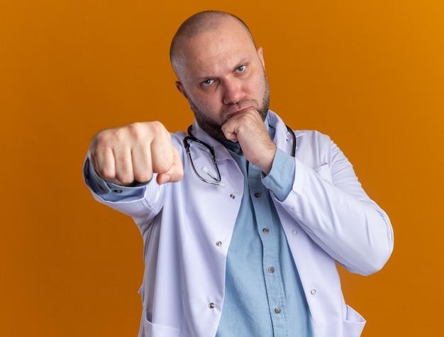 Marszczący brwi mężczyzna w średnim wieku, ubrany w szatę medyczną i stetoskop, wykonujący gest bokserski
