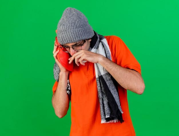 Marszczący brwi młody chory mężczyzna w okularach czapka zimowa i szalik zakładający torbę z gorącą wodą na twarz, wycierając nos ręką odizolowaną na zielonej ścianie