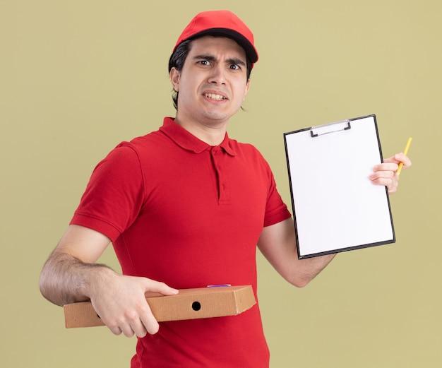 Marszczący brwi młody kaukaski dostawca w czerwonym mundurze i czapce, trzymający paczkę pizzy, pokazujący schowek z ołówkiem w dłoni