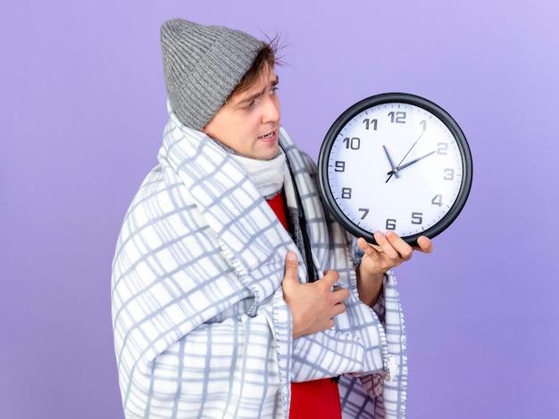 Marszczący brwi młody przystojny blondyn chory ubrany w czapkę zimową i szalik owinięty w kratę, trzymając i patrząc na zegar na fioletowym tle