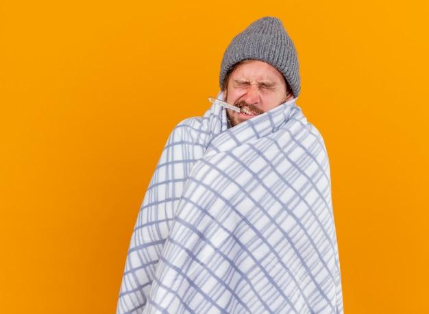 Marszczący brwi młody przystojny słowiański chory w czapce zimowej owinięty w kratę z termometrem w ustach z zamkniętymi oczami odizolowany na pomarańczowym tle z miejscem na kopię