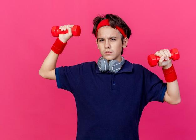 Marszczący brwi, młody przystojny sportowy chłopiec noszący opaskę i opaski na nadgarstki oraz słuchawki na szyi z aparatem ortodontycznym podnoszący hantle patrząc na przód odizolowany na szkarłatnej ścianie