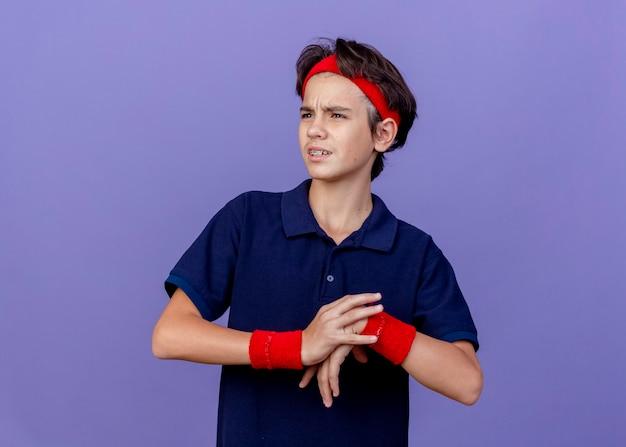 Marszczący brwi młody przystojny sportowy chłopiec noszący opaskę i opaski na nadgarstki z aparatami ortodontycznymi patrząc z boku kładąc rękę na innym ćwicząc na fioletowej ścianie z miejscem na kopię
