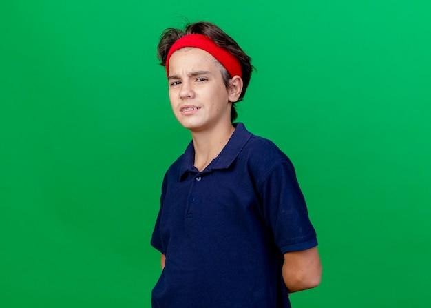 Marszczący brwi młody przystojny sportowy chłopiec noszący opaskę i opaski na nadgarstki z aparatem ortodontycznym trzymający ręce za plecami, patrząc na przód odizolowany na zielonej ścianie