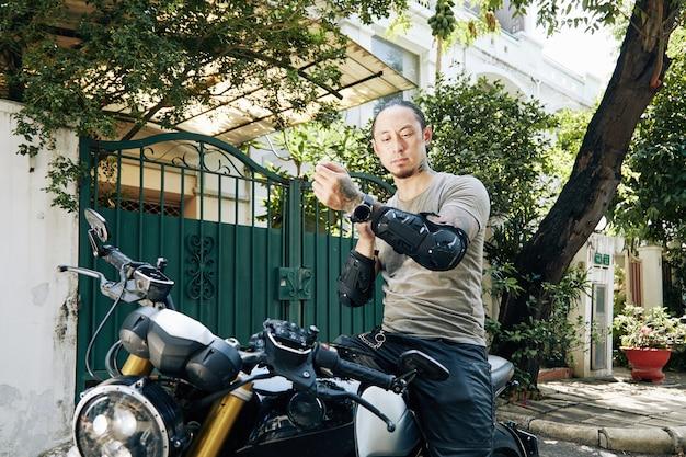 Marszczący brwi motocyklista zakładający ochraniacze na przedramiona dla ochrony podczas siedzenia na rowerze