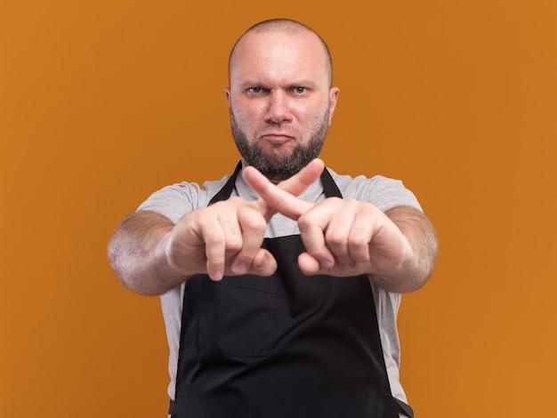 Marszczący brwi słowiański fryzjer w średnim wieku w mundurze pokazujący gest nie izolowany na pomarańczowej ścianie