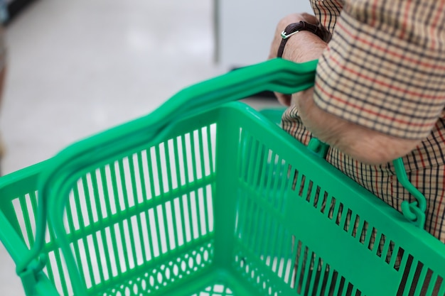 Marszczący starszy kobiety ręki mienia zakupy kosz w zakupy centrum handlowym