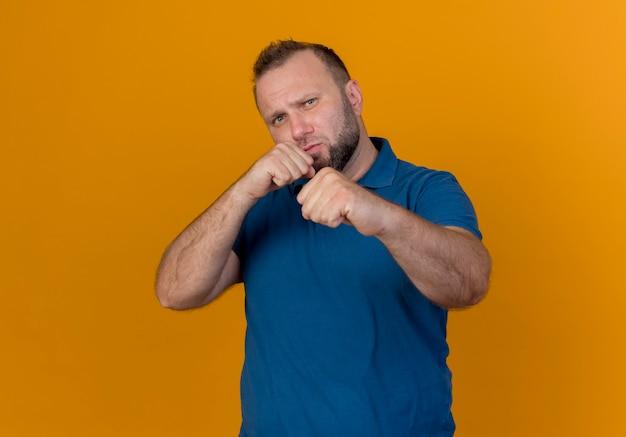 Marszczy brwi dorosły słowiański mężczyzna szuka i robi gest boksu