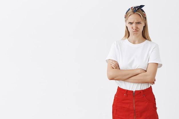 Marszczy brwi młoda blond dziewczyna pozuje pod białą ścianą