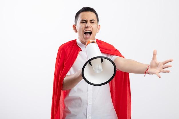 Marszczy brwi młody chłopak superbohatera w czerwonej pelerynie krzyczy w głośniku patrząc prosto wyciągając rękę na białym tle z miejsca na kopię