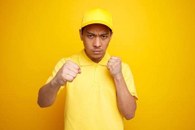Marszczy brwi młody człowiek dostawy czapkę i mundur robi gest boksu