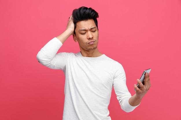 Marszczy brwi młody człowiek trzyma rękę na głowie, trzymając i patrząc na telefon komórkowy
