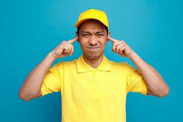 Marszczy brwi młody dostawca ubrany w mundur i czapkę trzyma palce w uszach