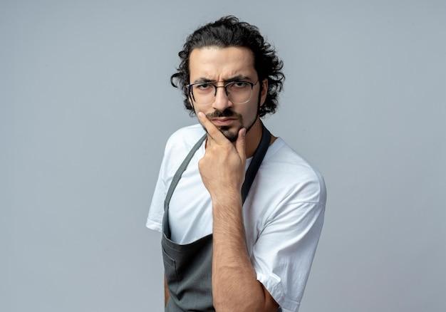 Marszczy brwi młody kaukaski fryzjer męski w okularach i falującej opasce do włosów w mundurze kładzie dłoń na brodzie na białym tle na białym tle z miejsca na kopię