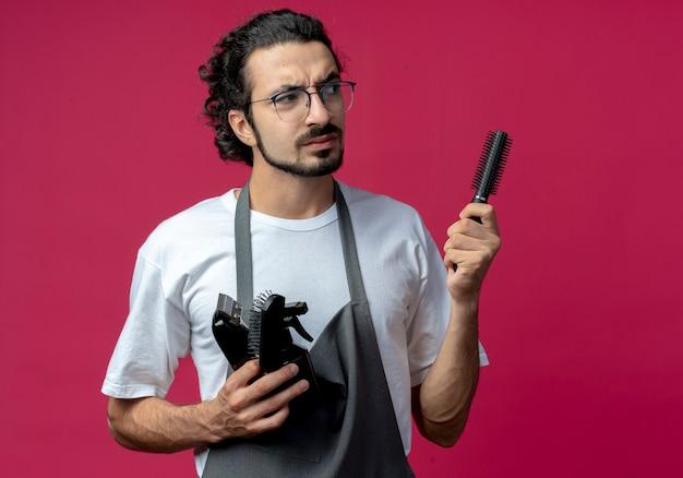 Marszczy brwi młody kaukaski fryzjer męski w okularach i falującej opasce do włosów w mundurze trzyma maszynkę do strzyżenia włosów, grzebień, butelkę z rozpylaczem patrząc na bok odizolowany na szkarłatnym tle z miejscem na kopię