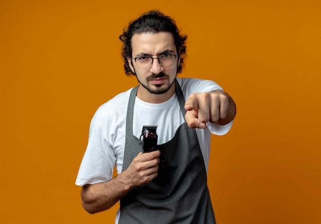 Marszczy brwi młody kaukaski fryzjer męski w okularach i falującej opasce do włosów w mundurze trzyma maszynkę do strzyżenia włosów i wskazuje na aparat odizolowany na pomarańczowym tle z miejscem na kopię