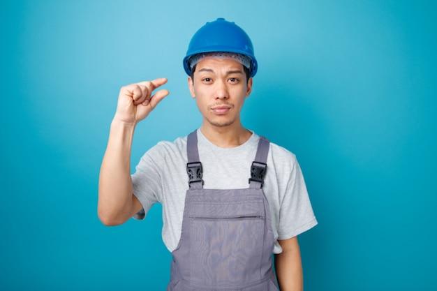 Marszczy brwi młody pracownik budowlany w kasku i mundurze robi niewielki gest