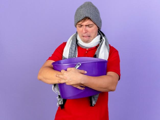 Marszczy brwi młody przystojny blondyn chory w czapce zimowej i szaliku trzyma plastikowe wiadro z zamkniętymi oczami i ma nudności odizolowane na fioletowej ścianie z miejscem na kopię