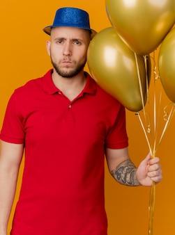 Marszczy brwi młody przystojny facet ubrany w kapelusz partii trzymając balony patrząc z przodu na białym tle na pomarańczowej ścianie