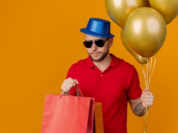 Marszczy brwi młody przystojny facet w okularach przeciwsłonecznych i kapeluszu, trzymając balony i papierowe torby na białym tle na pomarańczowej ścianie