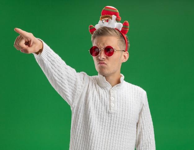 Marszczy brwi młody przystojny facet w opasce świętego mikołaja w okularach patrząc i wskazując na bok na białym tle na zielonym tle