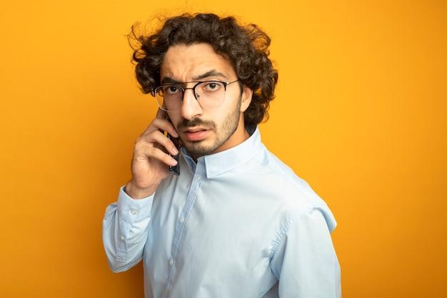 Marszczy brwi młody przystojny kaukaski mężczyzna w okularach rozmawia przez telefon, patrząc na kamery na białym tle na pomarańczowym tle z miejsca na kopię