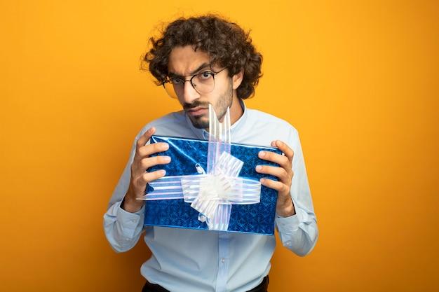 Marszczy brwi młody przystojny kaukaski mężczyzna w okularach trzyma paczkę na białym tle na pomarańczowej ścianie z miejsca na kopię