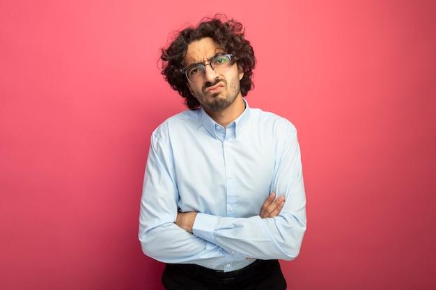 Marszczy brwi młody przystojny mężczyzna w okularach stoi z zamkniętą postawą patrząc z przodu na białym tle na różowej ścianie