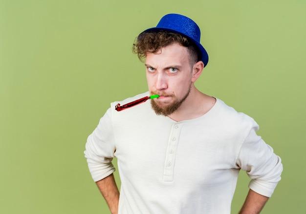 Marszczy brwi młody przystojny słowiański facet w kapeluszu imprezowym patrząc na kamerę dmuchanie dmuchawy trzymając ręce na talii odizolowane na oliwkowym tle z miejsca