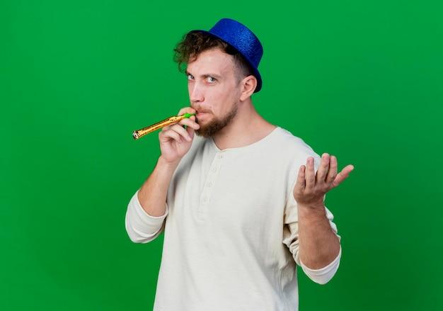 Marszczy brwi młody przystojny słowiański imprezowicz w kapeluszu imprezowym dmuchanie dmuchawa imprezowa patrząc z przodu pokazujący pustą dłoń odizolowaną na zielonej ścianie z miejscem na kopię