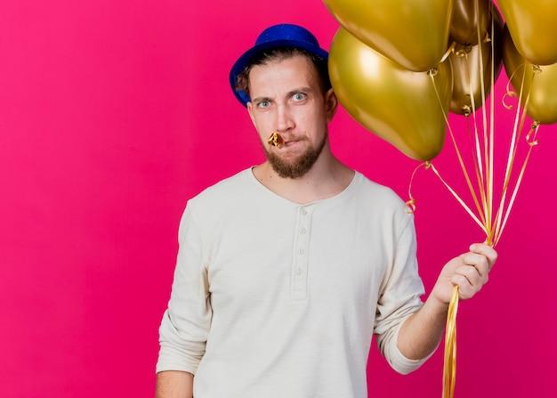 Marszczy brwi młody przystojny słowiański imprezowicz w kapeluszu imprezowym trzyma balony i dmuchawę w ustach, patrząc z przodu na białym tle na różowej ścianie z miejscem na kopię
