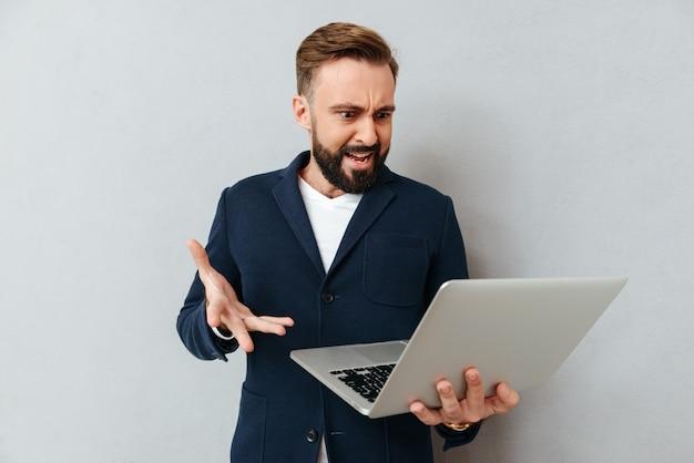 Marszczy brwi poważnego mężczyzna w kostiumu używać laptop odizolowywającego