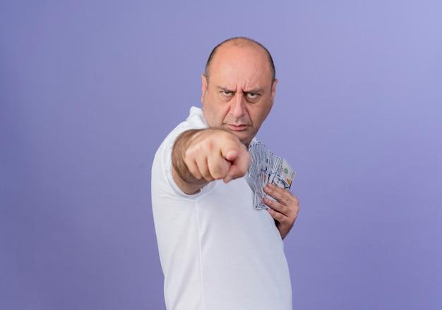 Marszczy brwi przypadkowy dojrzały biznesmen stojący w widoku profilu trzymając pieniądze i wskazując na aparat na białym tle na fioletowym tle z miejsca na kopię