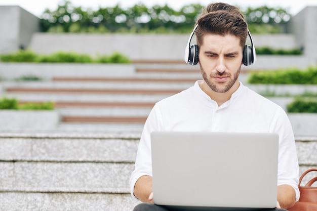 Marszczy brwi studentka siedzi na schodach kampusu i pracuje na laptopie