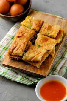 Martabak telor lub martabak telur. pikantne ciasto smażone na patelni nadziewane jajkiem, mięsem i przyprawami. martabak telur to jedna z indonezyjskich ulicznych potraw