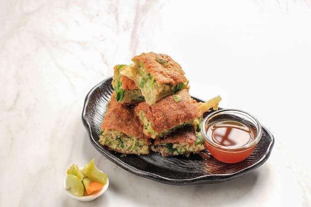 Martabak telur to popularne jedzenie uliczne w indonezji. jajko, dymka owijane cienką ciarem z mąki