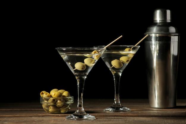 Martini w szklanym kieliszku z zielonymi oliwkami na szpikulcu na brązowym drewnianym stole. koktajle. bar