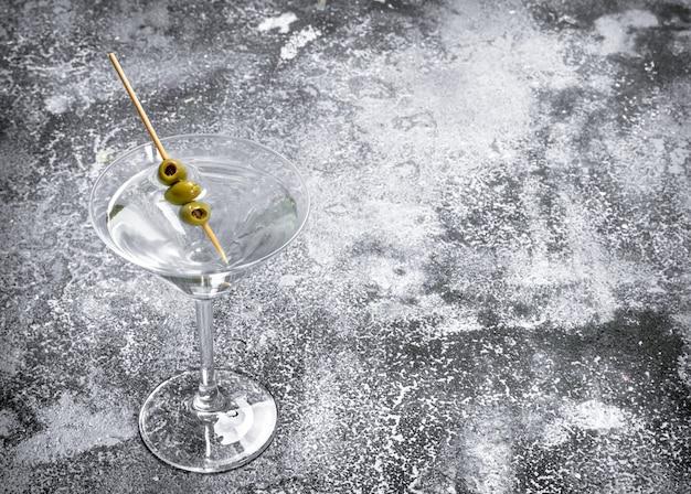 Martini z oliwkami na rustykalnym stole.