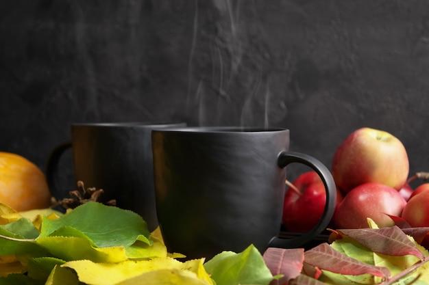 Martwa jesień dwa czarne kubki z gorącą herbatą w jesiennych żółtych liściach