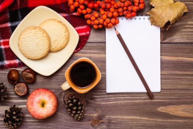 Martwa jesień: kawa, ciasteczka, kratka, notatnik i ołówek na drewnie