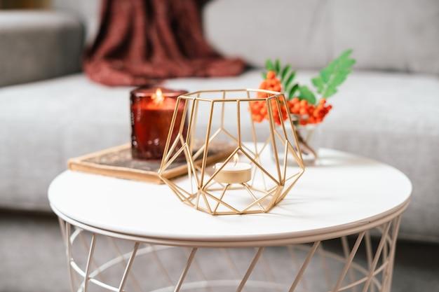 Martwa książka świeca jarzębina jagód i filiżanka herbaty lub kawy w salonie na stole w domu