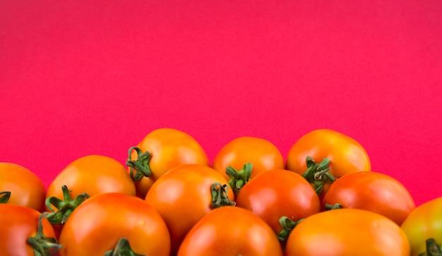 Martwa natura, artystyczna fotografia żywności. świeże pomidory z pięknym purpurowym różowym tłem.