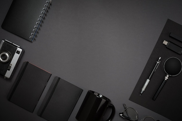 Martwa natura, biznes, materiały biurowe lub koncepcja edukacji: widok z góry obrazu notatnika, telefonu komórkowego i filiżanki kawy na czarnym tle, gotowy do dodania lub makiety