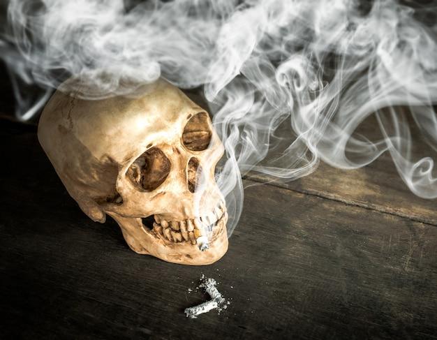 Martwa natura czaszki szkieletu z płonącym papierosem