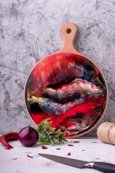 Martwa natura, deska do krojenia z czerwonym abstrakcyjnym wzorem, warzywa i przyprawy, nóż. styl rostik.