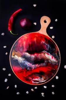 Martwa natura, deska do krojenia z czerwonym abstrakcyjnym wzorem, warzywa i przyprawy. styl rostik.