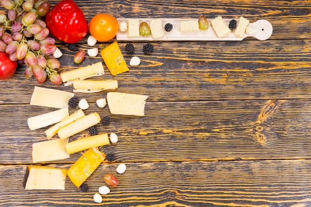 Martwa natura dla smakoszy - duży kąt różnorodności serów i świeżych owoców na rustykalnym drewnianym stole z miejscem na kopię